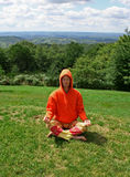 Meditating in garden. Meditating man on hill Royalty Free Stock Image