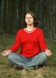 Meditating girl. Young girl meditating in lotus pose at the forest Royalty Free Stock Photos