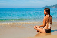 Meditating girl on the beach Stock Image