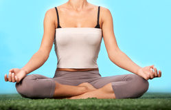 Meditating on grass. Lower part of slim female meditating in pose of lotus in isolation Stock Photography