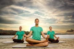 Meditating group. In lotus position outdoor Royalty Free Stock Image
