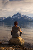 Meditating at Jackson Lake in Grand Teton National Park, Wyoming. Woman doing evening yoga at Jackson& x27;s Lake shore in Grand Teton National Park in Wyoming Royalty Free Stock Photography