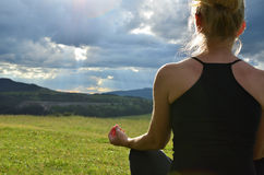 Meditating Lady on a Field. Image of a lady who is meditating in a mountain field faced to the sun behind stormy sky on west in the afternoon royalty free stock photo