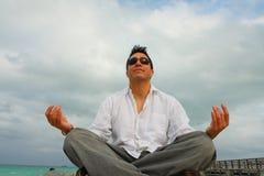 Meditating Man. Man meditating by the beach Stock Photos