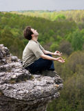 Meditating man. On the top of rock Royalty Free Stock Photography