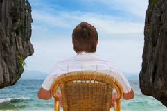 Meditating man beach looking at the sea. Meditating man sitting on a chair between rocks looking at the sea Royalty Free Stock Photo
