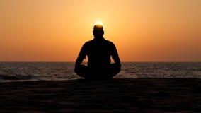 Meditating man on the beach Stock Photography