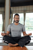 Meditating man. Bearded Indian man sitting in lotus position with his eyes closed Stock Photography