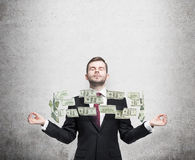Meditating man and flying dollar notes between his hands. Concrete background. Stock Photos