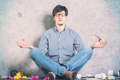 Meditating man. Handsome caucasian man meditating on messy desktop with concrete wall in the background Royalty Free Stock Images