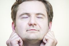 Meditating man holding his earlobes with fingers. Portrait of young Caucasian Ethnicity tranquil meditating man holding his earlobes on white background Stock Photography