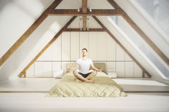 Meditating man in loft bedroom. Meditating man on bed in creative loft interior with white plank walls, wooden brown edging and windows with no view. 3D Royalty Free Stock Photos