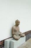 Meditating man. An old sculpture of meditating man Stock Photography
