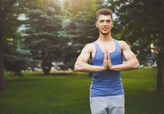 Meditating man with praying hands outdoors. Serene man practicing yoga and relaxing in park, copy space Royalty Free Stock Images