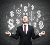 Meditating man, red tie, shining dollar signs Royalty Free Stock Images