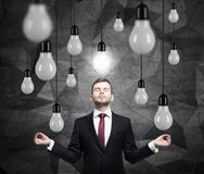 Meditating man is searching new ideas. Lots of light bulbs. Dark contemporary background. Stock Photos