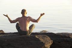 The meditating man on the seashore. The meditating man ashore the seas, sitting a back Stock Photography