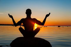 Meditating man silhouette on multicolored sunset background. Meditating man silhouette on vibrant sunset background. Multicolored summertime horizontal outdoors Royalty Free Stock Photo