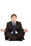 Meditating modern businessman sitting on floor Stock Images