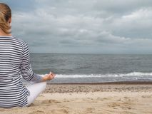 Meditating na praia imagens de stock royalty free
