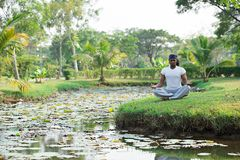 Meditating near the river Royalty Free Stock Image