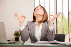 Meditating at the office. Stressed young business woman doing some breathing exercises and meditating at her office Stock Image