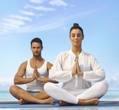 Meditating outdoors. Young couple meditating on the beach eyes closed Royalty Free Stock Image