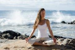Meditating pelo oceano Imagem de Stock