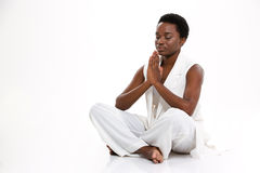 Meditating pretty african american young woman sitting in yoga pose Stock Photos