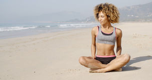Meditating On The Sea Coast. Girl meditating on the sea coast sitting in yoga position Royalty Free Stock Photo