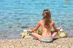 Meditating by the see. Girl meditating by the sea on the beach Stock Images