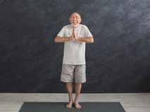 Meditating senior man with praying hands indoors. Meditating senior man with praying hands. Serene elderly guy practicing yoga and relaxing indoors, black Stock Photo