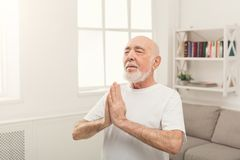 Meditating senior man with praying hands indoors. Meditating senior man with praying hands. Serene elderly guy practicing yoga and relaxing at home. Active Royalty Free Stock Images