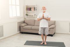 Meditating senior man with praying hands indoors. Meditating senior man with praying hands. Serene elderly guy practicing yoga and relaxing at home. Active Royalty Free Stock Photography