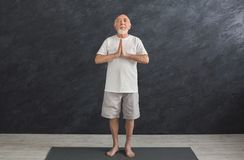 Meditating senior man with praying hands indoors. Meditating senior man with praying hands. Serene elderly guy practicing yoga and relaxing indoors, black Royalty Free Stock Photo