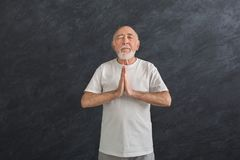 Meditating senior man with praying hands indoors. Meditating senior man with praying hands. Serene elderly guy practicing yoga and relaxing indoors, black Royalty Free Stock Photography