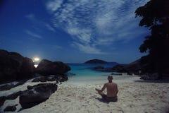 Meditating on shore of night ocean Stock Photos