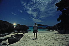 Meditating on shore of night ocean Stock Images