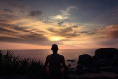 Meditating on shore of  ocean Royalty Free Stock Image