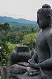 Meditating sitting Buddha sculputre in stone at Stock Image