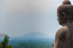 Meditating sitting Buddha in stone above jungle at Royalty Free Stock Photography