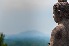 Meditating sitting Buddha in stone above jungle at Royalty Free Stock Images