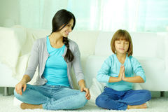 Meditating. Smiling mother looking at her daughter how she meditating Royalty Free Stock Photography