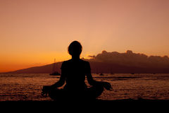 Meditating in Sunset. A woman meditating on the maui coastline at sunset Stock Image