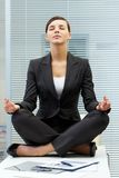 Meditating on table. Image of young employer on workplace and meditating Royalty Free Stock Photos
