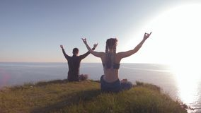 Meditating together, young man and woman in sunlight sitting in lotus position on land on top of mountain looking at sea