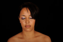 Meditating Woman. A portrait of a meditating African American woman, on black studio background Royalty Free Stock Image