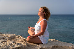 Meditating woman. Woman meditating with closed eyes, hands spread Royalty Free Stock Photo
