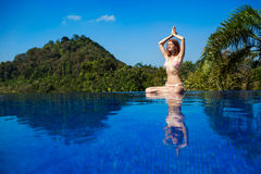 Meditating. Woman doing yoga. Woman doing yoga and meditating in the lotus position Stock Image