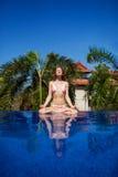 Meditating. Woman doing yoga. Woman doing yoga and meditating in the lotus position Stock Photos